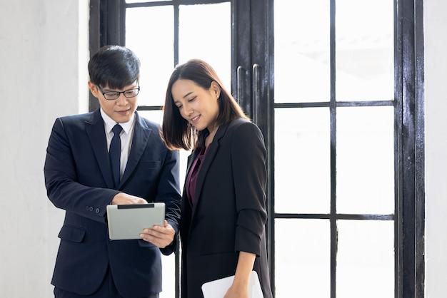 Бизнесмен и бизнесвумен, используя ноутбук вместе, стоя у окна в офисе
