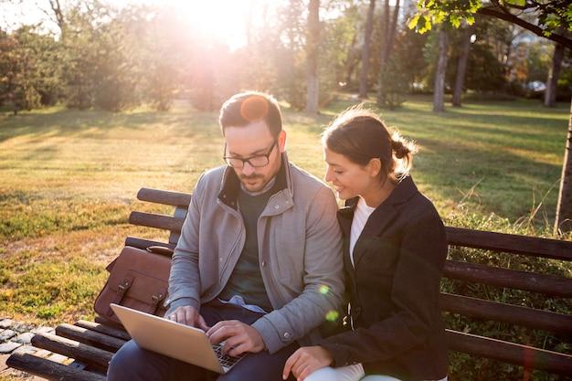 Бизнесмен и предприниматель, используя ноутбук, сидя на скамейке в парке