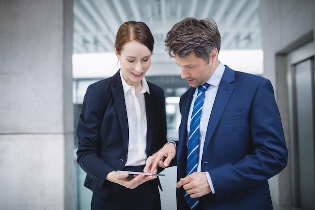 사업가 및 디지털 태블릿을 통해 논의하는 동료