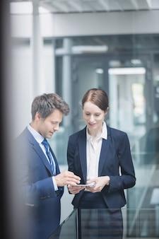 Бизнесмен и коллега обсуждают на цифровой планшет