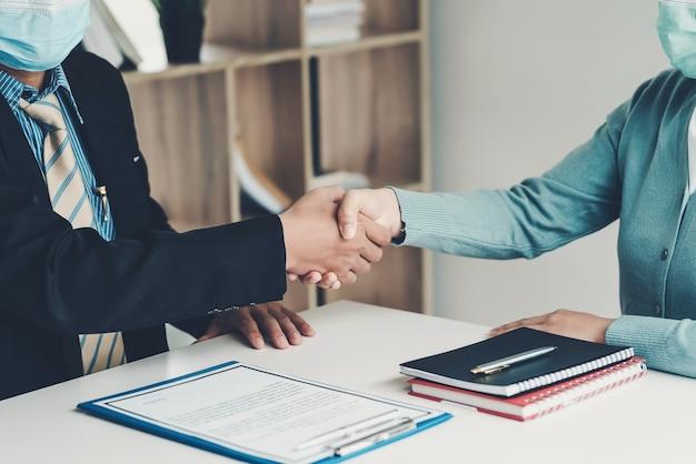 ビジネスマンと顧客が手を振って、オフィスで一緒にうまく働くことに同意します。マスクを着用してください