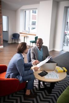 사업가이자 경제학자. 노트북을 들고 탁자에 앉아 협상을 하는 사업가와 경제학자