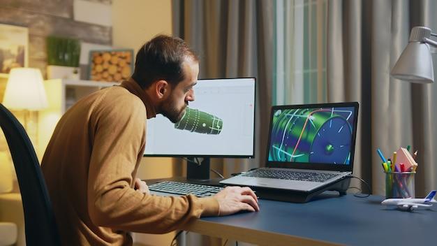 사업가와 엔지니어는 현대적인 소프트웨어를 사용하여 밤에 홈 오피스의 컴퓨터에 터빈을 설계합니다.