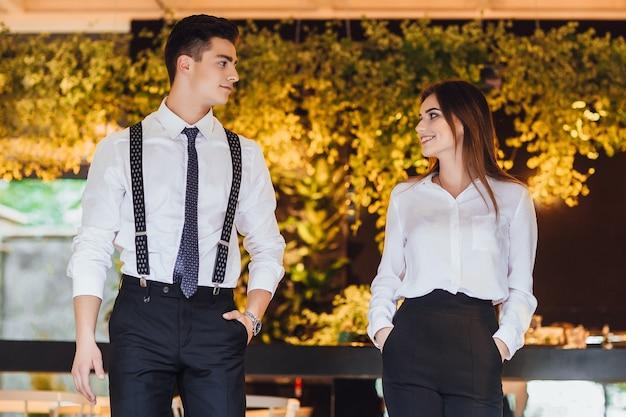 現代のオフィスで白いシャツを着たビジネスマンと彼のアシスタントは、ドキュメントを確認し、仕事について話し合う
