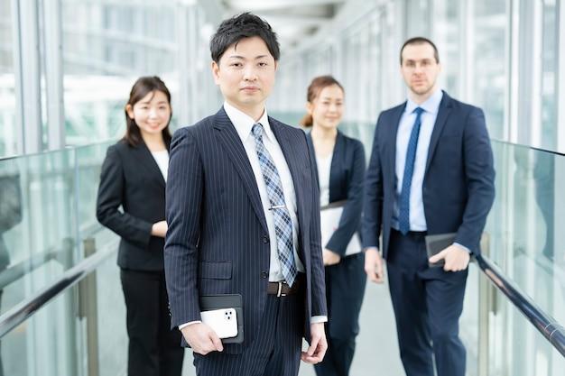 Бизнесмен и его бизнес-команда, стоя в офисной зоне