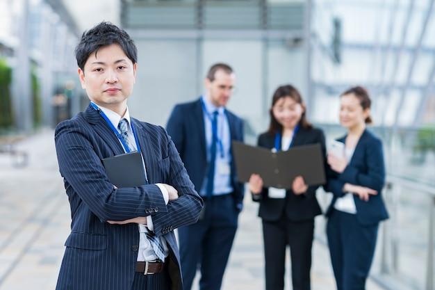 ビジネスマンと彼のビジネスチームがオフィスエリアに立っています