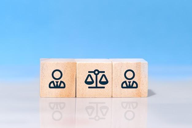 Бизнесмен и иконы закона на деревянных кубиках на синем фоне. понятие иска, судебного конфликта, спора или судебного преследования в бизнесе