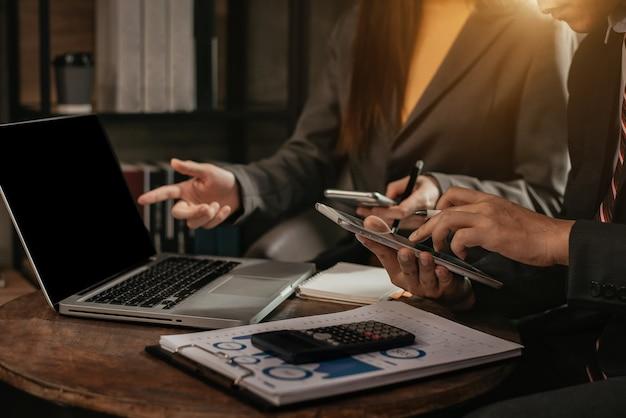 Бизнесмен и партнер с помощью планшета и калькулятора для расчета финансов, налогов, бухгалтерского учета, статистики и аналитических исследований концепции.