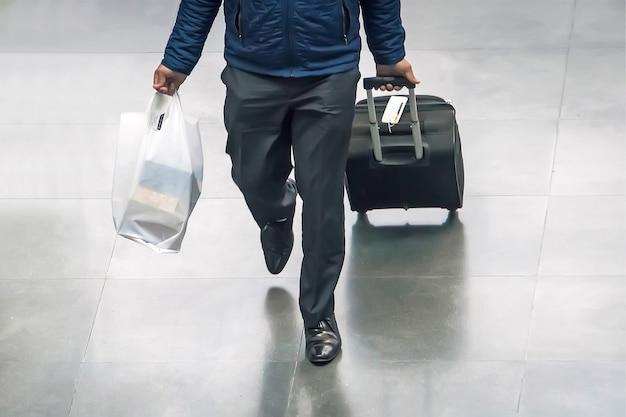 旅行のコンセプト、夏休みのコンセプト、空港ターミナルの旅行者用スーツケースを備えた、空港出発ラウンジのビジネスマンとスーツケース。車輪付きのスーツケースと手に白いバッグを持った旅行者。