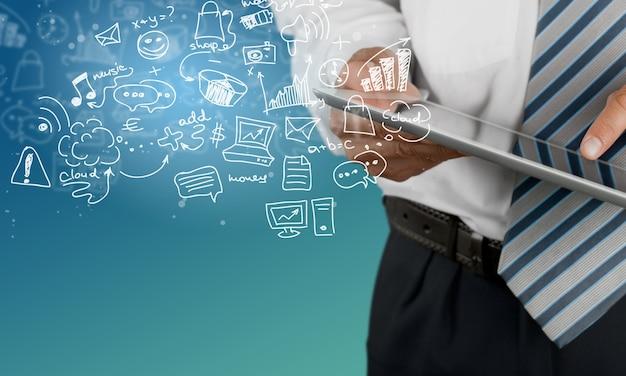 背景に抽象的なビジネスアイコンスケッチを持つビジネスマンとタブレットのpc
