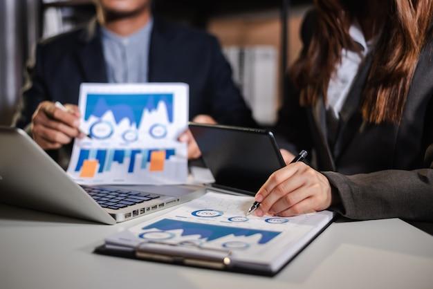 財務諸表の財務タスクを分析するビジネスマンとチーム。スマートフォンとラップトップとタブレットで。ウェルスマネジメントのコンセプト