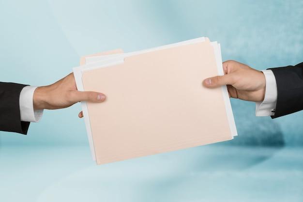 Бизнесмен и женщина, вручая папку с бумажными файлами