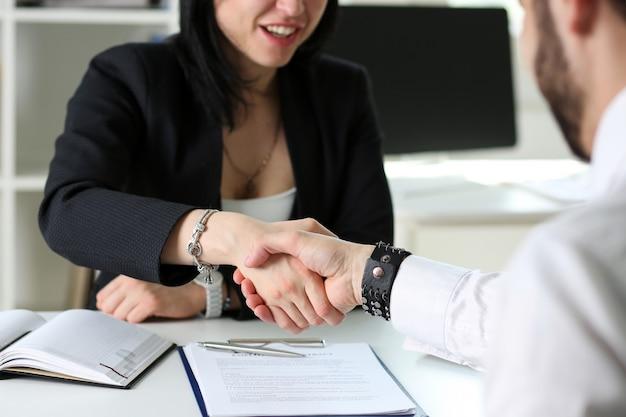 ビジネスマンおよび女性はオフィスでこんにちはとして握手