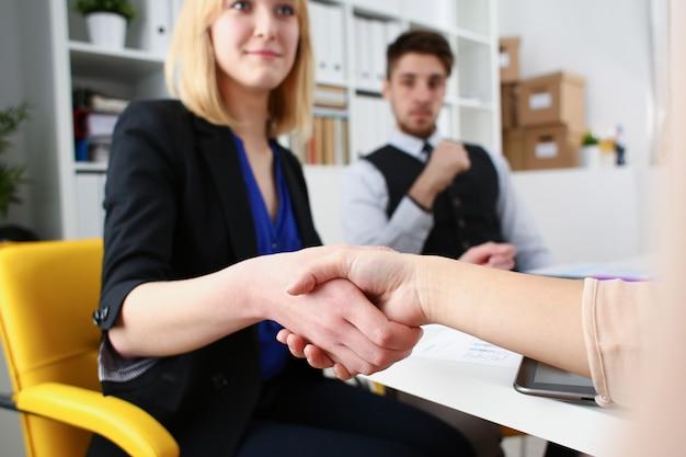 Бизнесмен и женщина пожимают друг другу руки как привет