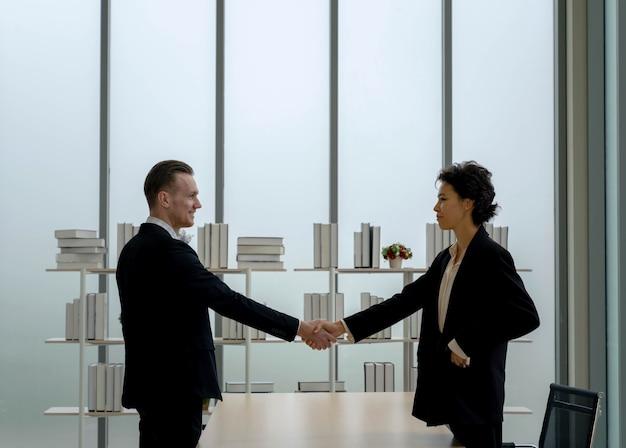 사업가와 여성이 현대 사무실에서 탁자 위에 서서 악수를 하고 있습니다. 비즈니스 계약 성공. 조직 간의 협업. 팀 리더. 금융 계약.