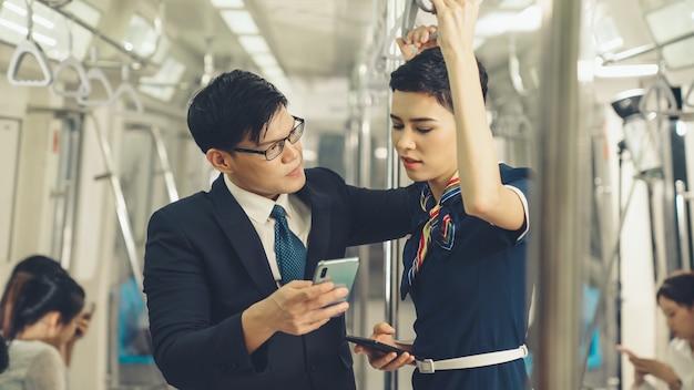 公共の電車で話しているビジネスマンと女性
