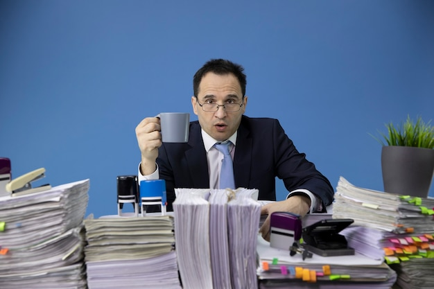 Businessman angrily looking at the front with cup of coffee in his hand at desk full of paperwork