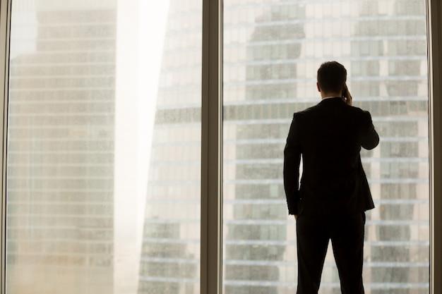 Бизнесмен отвечая на конфиденциальный звонок в офисе