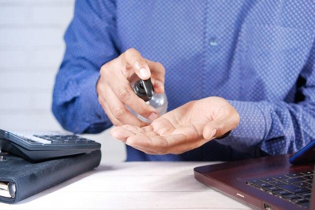 노트북을 사용하기 전에 소독제 액체를 바르는 사업가