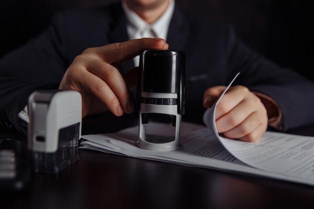 ビジネスマンは利益契約を承認します。机の上のコイン、契約書、切手のスタック