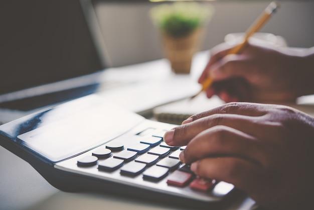 ビジネスマンは電卓とドキュメントで作業しています。進行中の会議レポート。オフィスビジネスコンセプトで