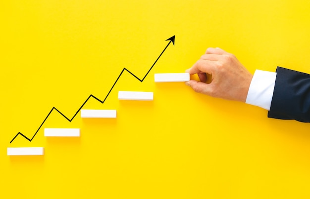 成長矢印とステップ階段としてウッドブロックを配置するビジネスマン