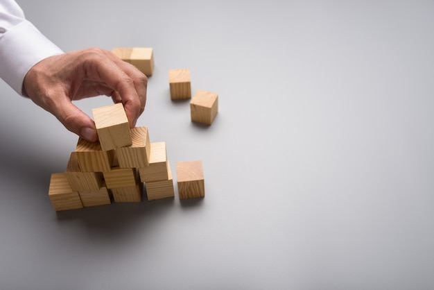 灰色の背景にピラミッド型の木製キューブを配置するビジネスマン。画像右側にコピースペースあり。