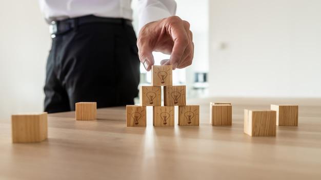 ビジネスマンのオフィスの机の上の電球のアイコンが付いた木製キューブを配置する