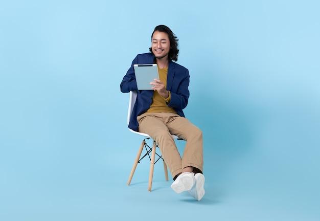 明るい青色の背景に分離された椅子に座ってデジタルタブレットを使用して笑顔のビジネスマンアジア人幸せ。