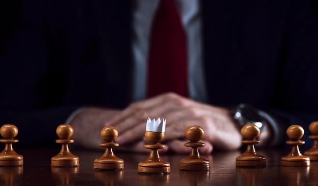 彼の頭に紙の王冠を持つポーンの前にチェス盤でビジネスマン