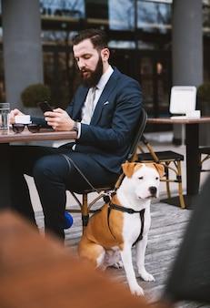 Бизнесмен в кафе с собакой. лучшие друзья в кафе.
