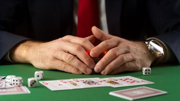 カジノでポーカーとブラックジャックをプレイするゲームチップ、カード、サイコロと緑のゲームテーブルのビジネスマン