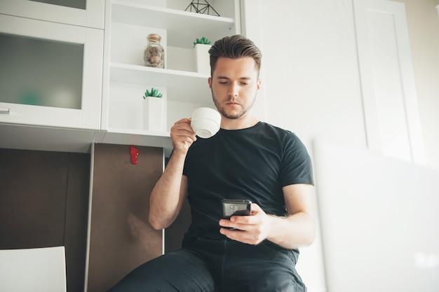 自宅で電話を使用し、電話のコンピューター技術を使用してコーヒーを飲むビジネスマンは...