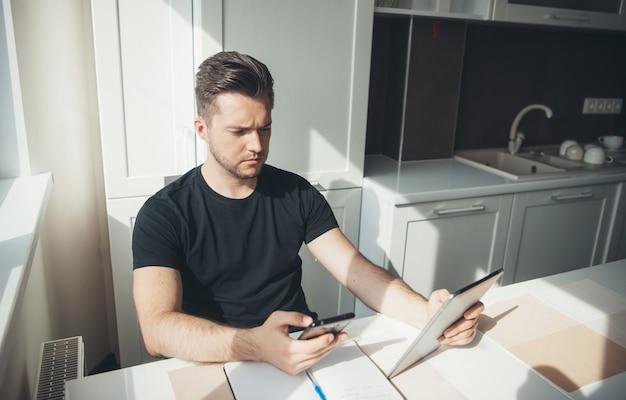 Бизнесмен дома, используя телефон для чата делового общения внештатный рабочий домашний офис онлайн ...