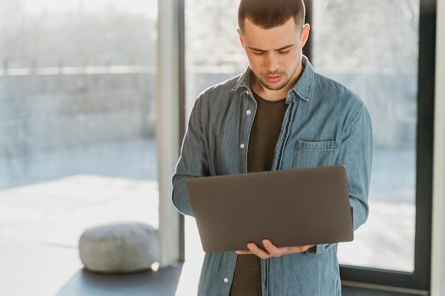 ノートパソコンを持つオフィスでビジネスマン