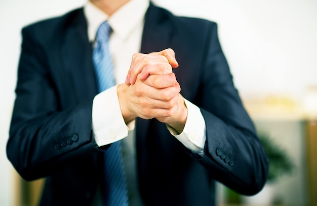 Бизнесмен в офисе со сложенными руками. готовность к дружбе и сотрудничеству.