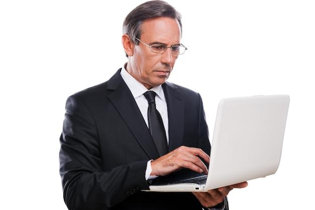 Бизнесмен на работе. уверенный зрелый мужчина в формальной одежде, работающий на ноутбуке, стоя на белом фоне