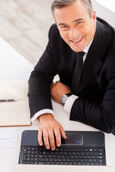 Бизнесмен на работе. вид сверху счастливого зрелого человека в формальной одежде, работающего на ноутбуке и улыбающегося, сидя на своем рабочем месте