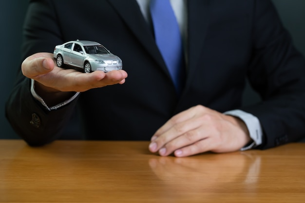 Businessman in bank holding car model, new car hire purchase loan concept.