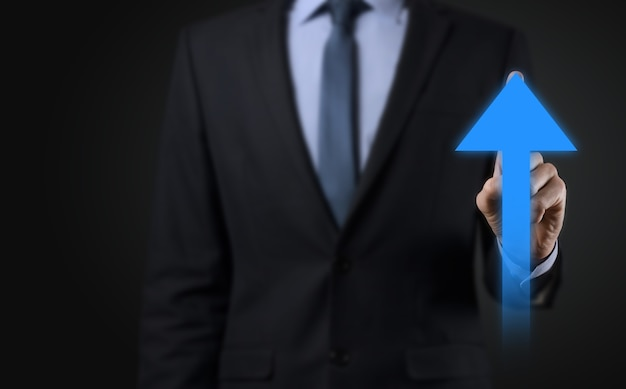 Businessman on a black background presses, presses a finger on a positive growth arrow. graphs of indicators. business development and finance concept.