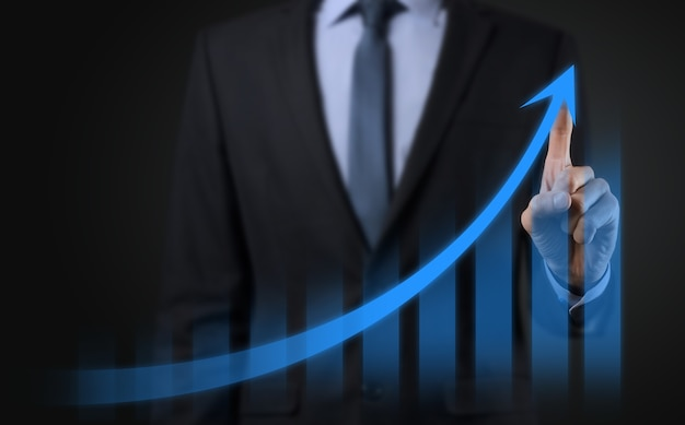 Businessman on a black background presses, presses a finger on a positive growth arrow