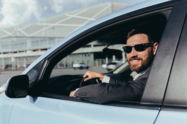 Businessman in black glasses sitting behind the wheel of a car