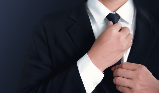 Businessman in black suit and adjusting necktie.