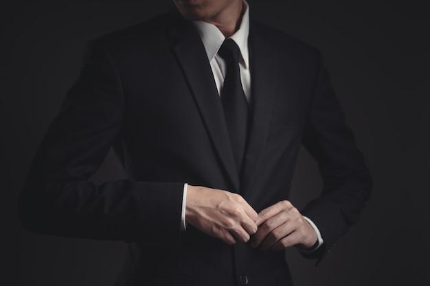 Businessman in black suit on black