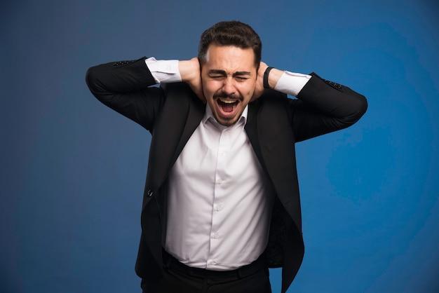Uomo d'affari in abito nero che copre le orecchie e urla.