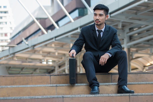 Businessman in black suit and his briefcase bag sit on stair in city