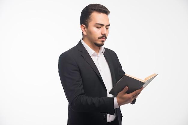 Uomo d'affari in abito nero che tiene la sua lista di compiti e controllarla.