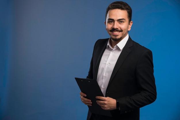 Businessman in black suit holding the tasklist.