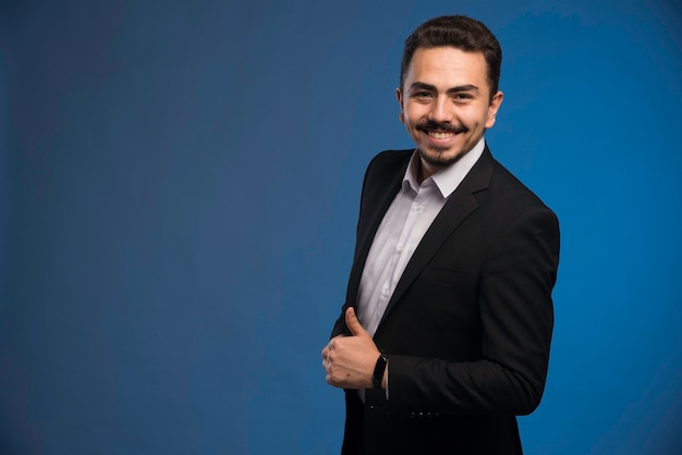 Businessman in black suit makes thumb up.
