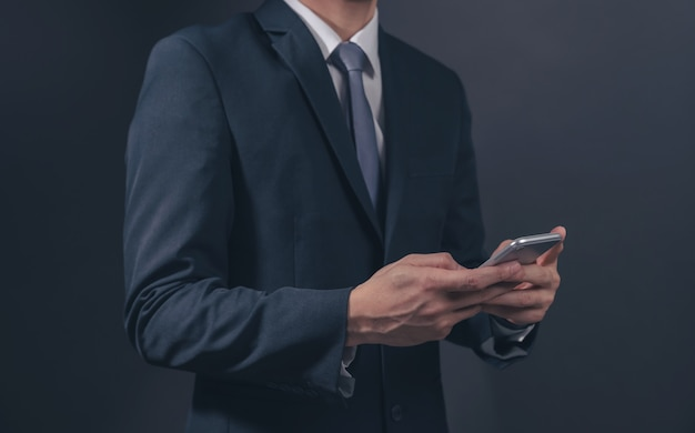 Businessman in black suit and necktie with holding smartphone on black background.